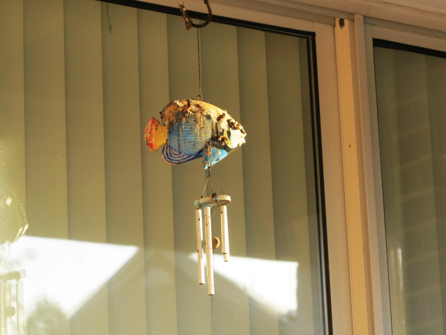 A fish windchime, covered in bird crap.